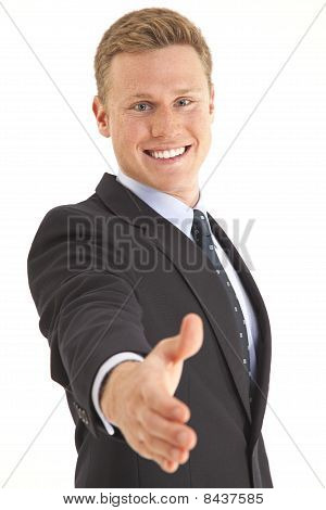 Young businessman holding out hand for a shake