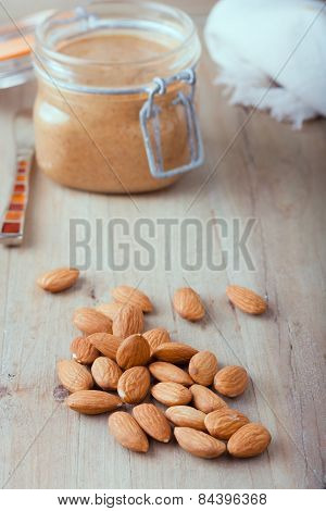 raw organic almonds with almond butter at the background