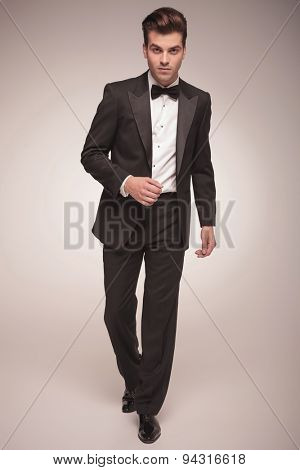 Full body picture of a handsome young business man walking on grey studio background, looking at the camera.