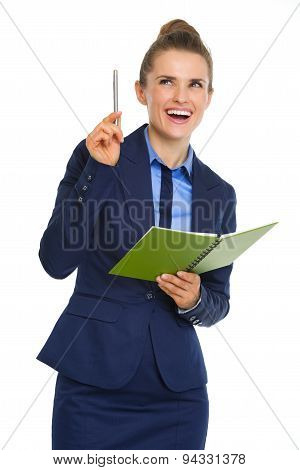Businesswoman Holding Open Notebook And Pen Having Aha Moment