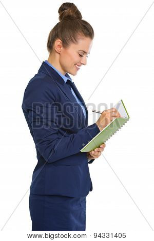 Smiling Businesswoman In Profile Standing, Writing In Notebook
