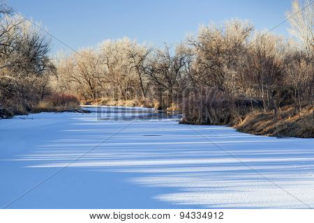 frozen Cache la Poudre River in Fort Collins, Colorado with shadow patterns on ice