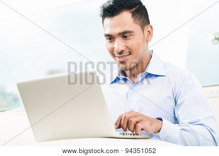 Businessman working with laptop from home being a telecommuter