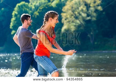Man and woman skimming stones on river in summer