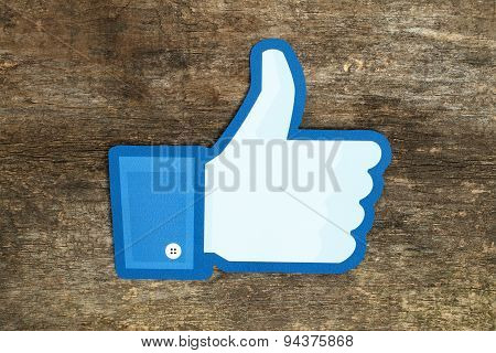 KIEV UKRAINE - APRIL 15 2015: Facebook thumbs up sign printed on paper and placed on wooden backgrou