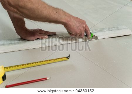 Man Cuts Off A Piece Of Drywall