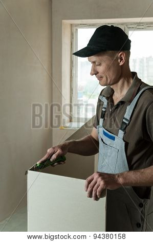 Worker Cuts A Piece Of Drywall