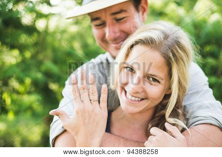 Happy blonde woman showing engagement ring poster