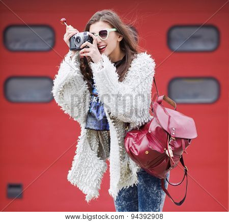female photographer with professional SLR camera, natural light, selective focus on nearest part of