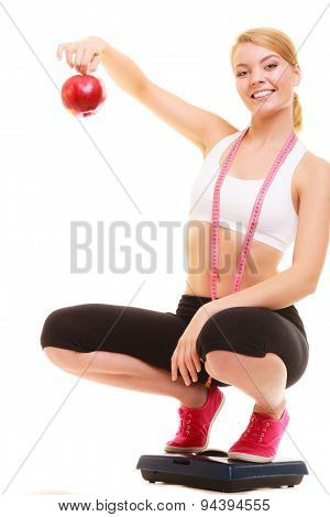 Happy joyful young woman girl with measuring tape on weighing scale holding apple. Slimming and dieting. Healthy lifestyle nutrition concept. Isolated on white background. poster
