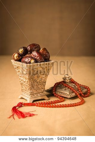 Ramadhan objects. Ripen dates in a decorative Islamic jar and prayer beads.