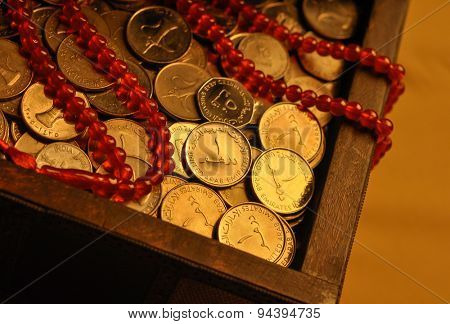 Charity during holy month of Ramadan. Close up of UAE Dirham coins in a vintage chest with prayer beads.