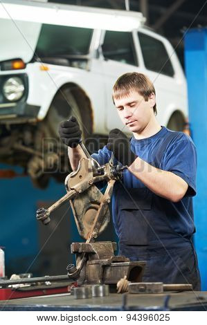 automotive mechanic worker tighten screw with spanner during automobile car maintenance at lever repair service station poster