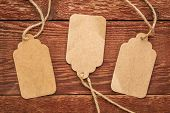 three blank paper price tags with a twine against planks of rustic barn wood poster