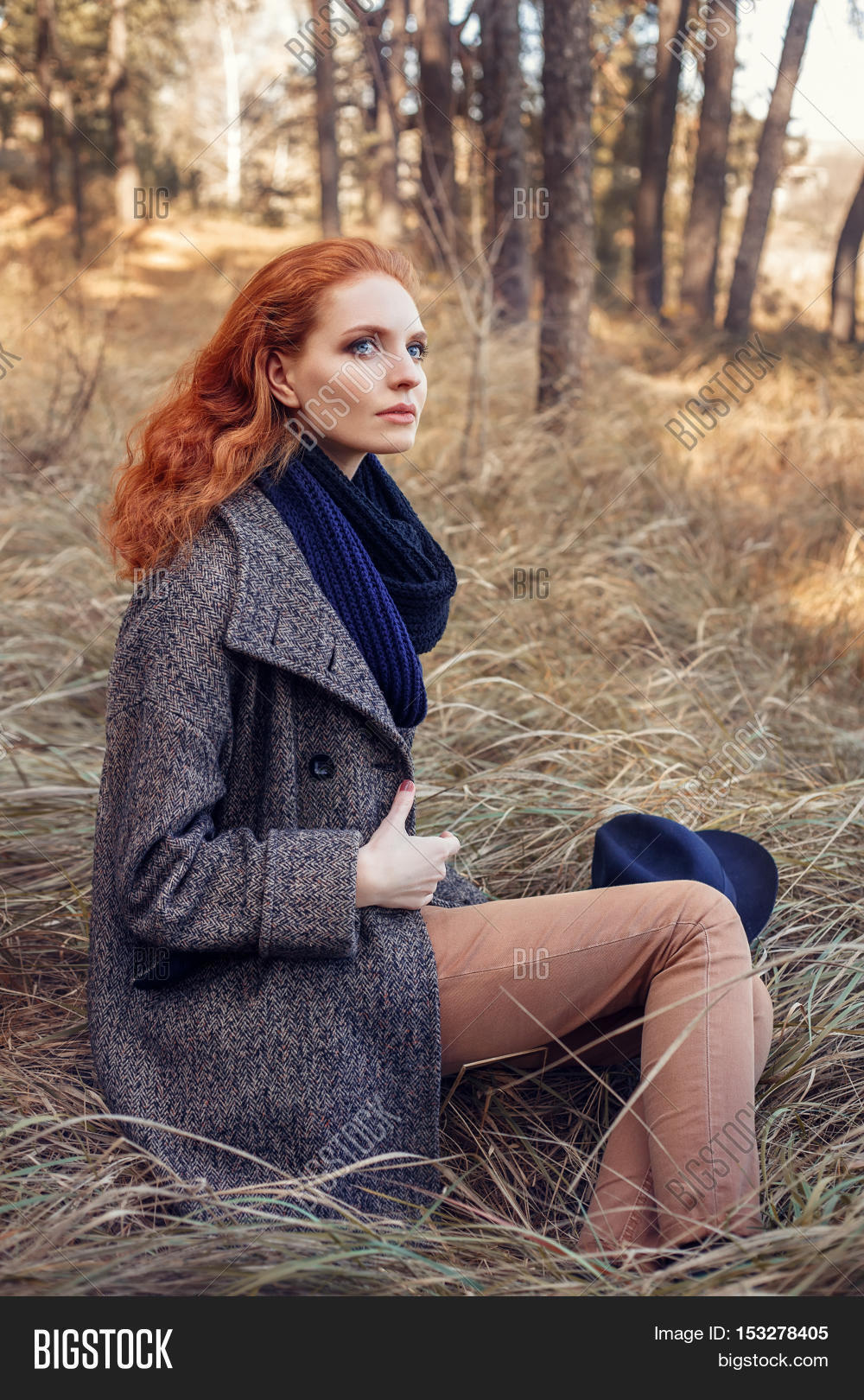 9c0fdc0592760 Beautiful red-haired woman. Redhead girl in autumn clothes in the forest.  Redhead