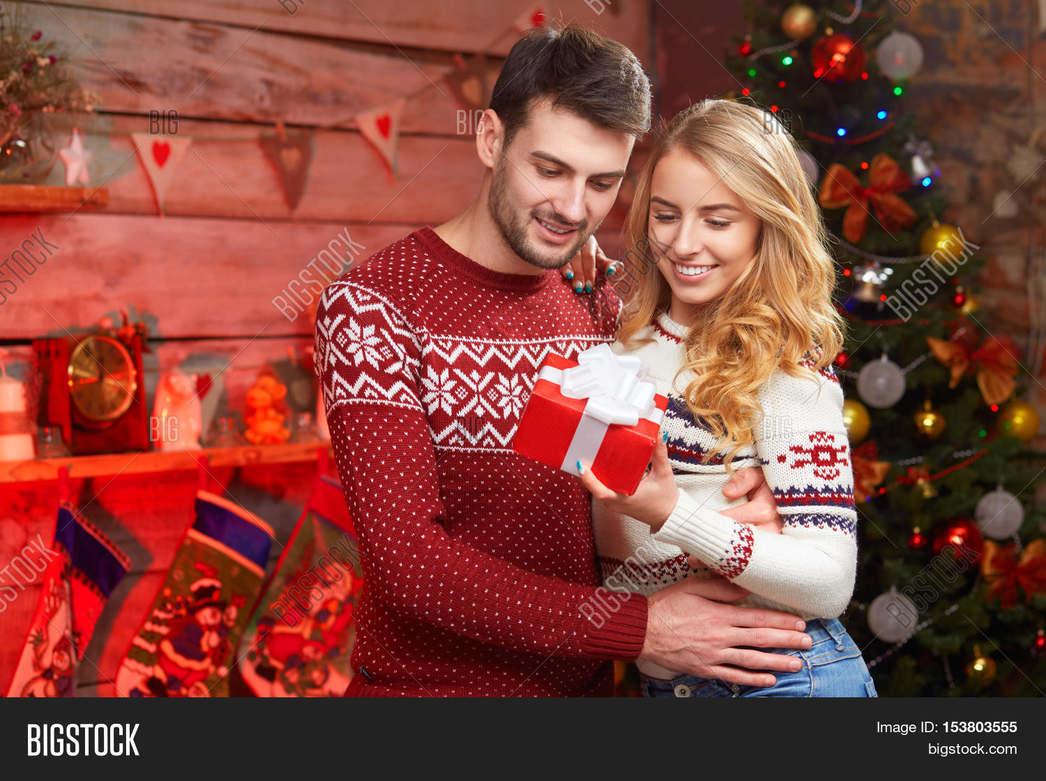 young couple sharing christmas present young family embracing and holding red gift box with decorations