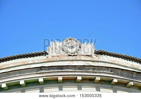 Hammer and Sickle in conjunction with the emblem of the USSR of the concrete on the roof of the old building .