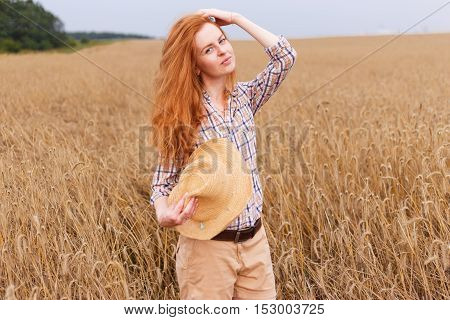 Young red hair beautiful woman in golden wheat field