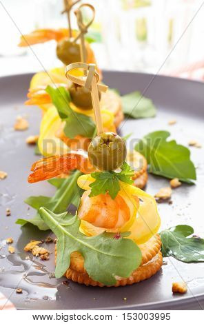 Prawn canapes with arugula leaves and olives.