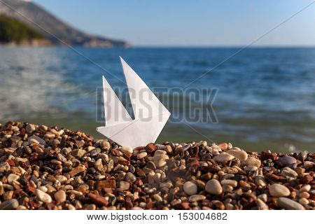 White paper boat on a sand beach