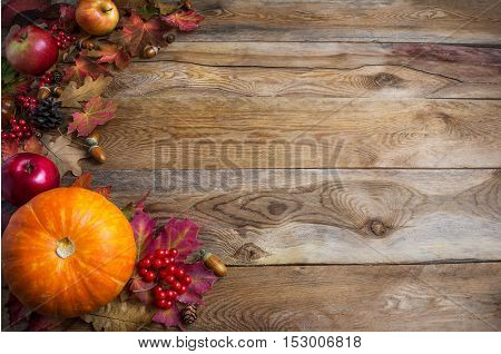 Thanksgiving or fall greeting background with orange pumpkins and fall leaves. Thanksgiving background with seasonal vegetables and fruits. Fall background. Copy space