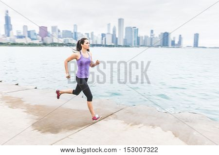 Woman Jogging With Chicago Skyline On Background, Panning