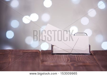 Professional blank business cards in holder stands on wooden table on a abstract gray background.