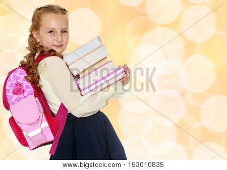Beautiful small girl schoolgirl in black skirt and white blouse goes to school. Behind the girl a big red schoolbag , holding her stack of books. Close-up.Brown festive, Christmas background