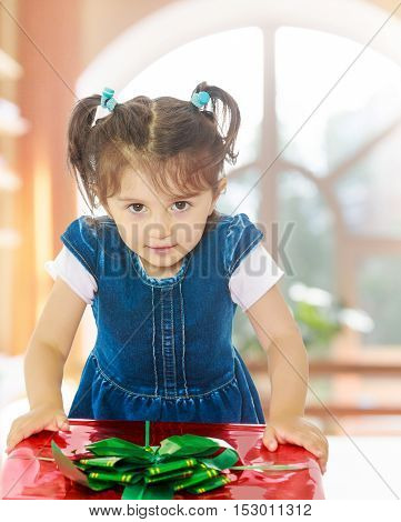Caucasian little girl in a blue dress with short sleeves , kneeling around a red box with a bow. Close-up.In a room with a large semi-circular window.