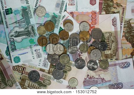 Banknotes and coins coins of different denomination arranged disorderly