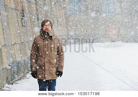 big man with a beard and glasses in winter clothes enjoys the snow cold snowfall blizzard
