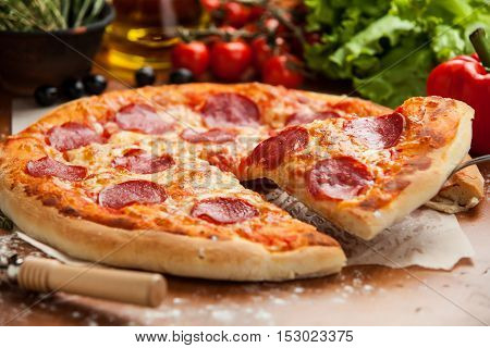 Salami pizza lifted 1 slice on the table decorated with vegetables and oil