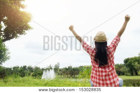 A happy man is relaxing on green grass with hat and raised up to sky arms at sunny summer day at park background. Concept of wellbeing and healthy lifestyle