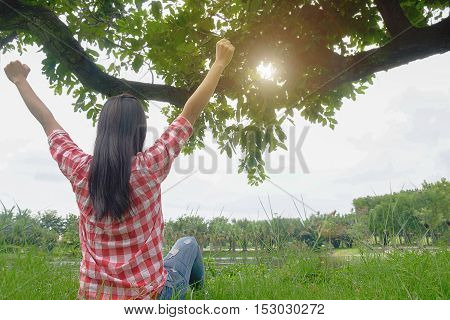 A happy asian woman is relaxing on green grass with hat and raised up to sky arms at sunny summer day at park background. Concept of well being and healthy lifestyle. Relaxing concept.