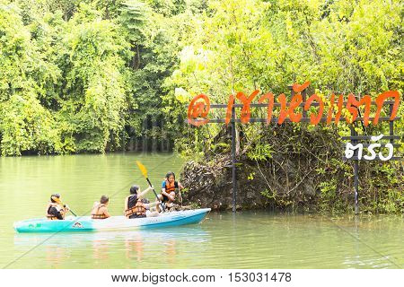 Koaw-Hua-Tag,October-20-2016,Travelers with a canoe and flag of Koaw-Hua-Tag,Trang province of Southern Thailand.01