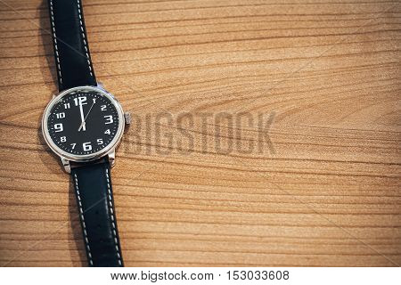 wristwatch on wooden table with blank space for text on the right side - clock face show the time at noon or midnight