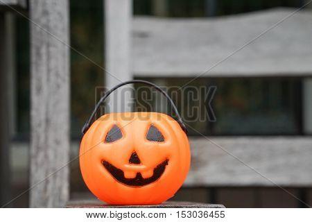 close up orange Jack-O-Lantern on wooden bench