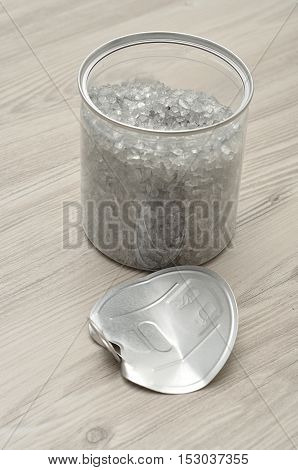 An open see through tin with a metal lid tin next to it on the table filled with Grey glass sand