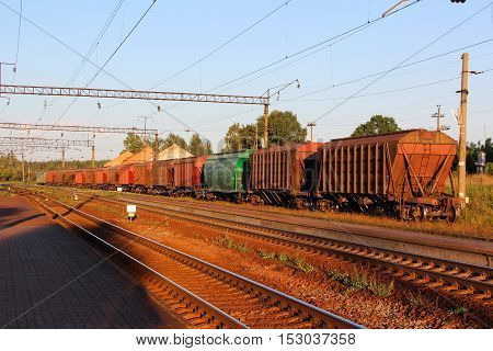 Long Container Train with oil, fuel, grain at Sunrise on small station in Belarus