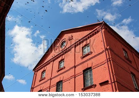 The building of the old watermill of red brick. View from below on a blue sky with a huge flock of birds.