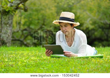 Happy middle aged woman lying on green grass using tablet computer in the park