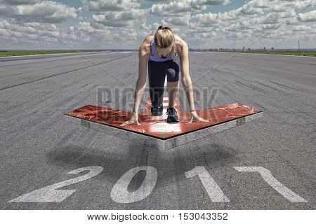 Female runner kneels in start position on a red floating arrow platform which is placed above an airport runway surface. The runway surface shows the date of the year 2017.