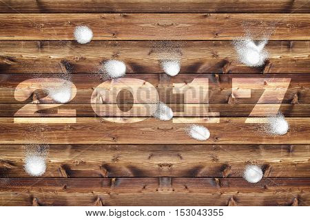 Wooden board with bleached out 2017 letters which is bombarded with snowballs.