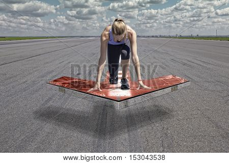 Female runner kneels in start position on a red floating arrow platform which is placed above an airport runway surface.