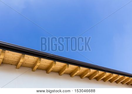 Low angle view of new house with wooden roof and gutter against clear blue sky