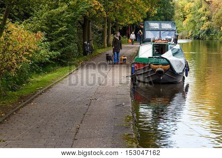 NOTTINGHAM ENGLAND - OCTOBER 19: Woman standing by boat on Nottingham canal. In Nottingham England. On 19th October 2016.