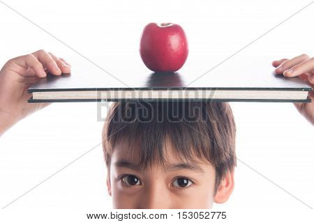 Little boy with apple on the book on his head education concept back to school