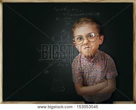 Emotional pupil boy near the chalkboard with formulas written on it