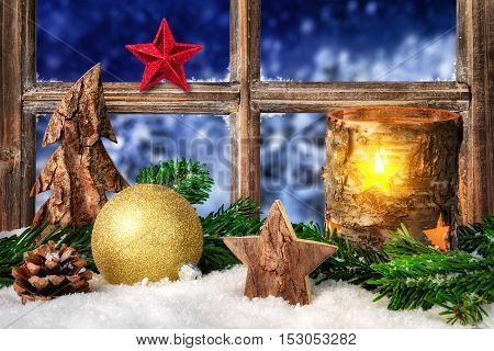 Christmas Advent or winter seasonal arrangement on a window sill in cozy candle light decorated with snow ornaments and fir branches