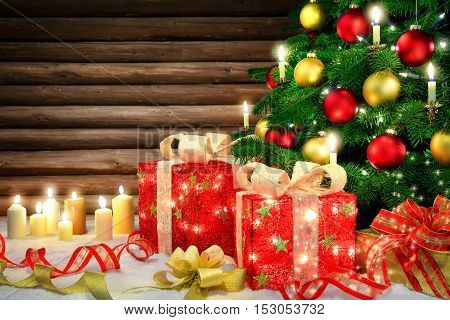Shiny Christmas scene with a Christmas tree candles ornamental gift boxes with lamps bows snow and a rustic wooden wall background
